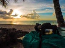拍海滩日落的照片的照相机 免版税库存照片