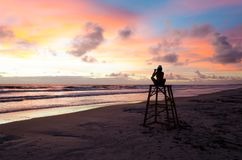 拍海的照片一名现出轮廓的妇女在一个海滩的一个救生员塔顶部与太阳上升 图库摄影