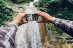 拍瀑布的照片与他的智能手机发展技术的人的手旅游业概念的 免版税库存图片