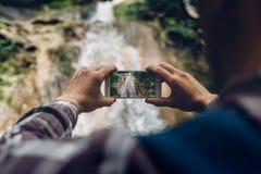 拍瀑布的照片与他的智能手机发展技术的旅客的手旅游业概念的 库存照片