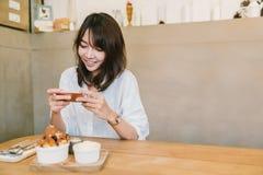 拍点心的照片逗人喜爱的亚裔女孩在咖啡店 娱乐活动或手机摄影,食物照片概念 免版税库存图片