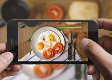 拍煎蛋的照片与手机的 库存照片