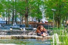 拍照片在周年纪念公园,在C的环境美化的空间的妇女 库存图片