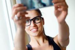 拍照片她自己的逗人喜爱的深色的妇女 免版税库存照片