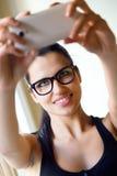 拍照片她自己的逗人喜爱的深色的妇女 免版税库存图片