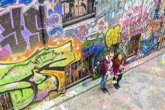 拍照片用智能手机在laneway的selfie棍子的游人 库存照片