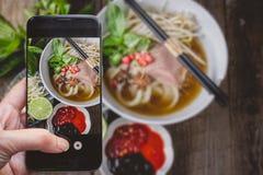 拍照片由按在照片的P智能手机的手指 免版税库存图片