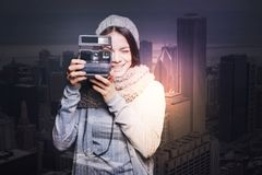 拍照片的一个温暖的帽子的快乐的微笑的妇女 免版税图库摄影