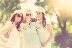 拍照片的三个可爱的女孩暑假 免版税库存图片