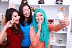 拍照片的三名美丽的妇女使用移动电话照相机 免版税库存照片