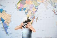 拍照片的上尉帽子的滑稽的小男孩由老减速火箭的影片照相机在地图附近 库存图片