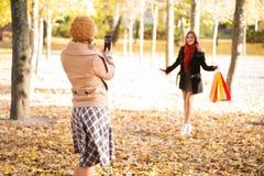 拍照片的两名妇女在秋天森林里 免版税库存照片