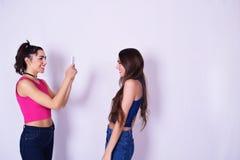 拍照片的两名时髦的妇女 湿背景概念黑暗的友谊鹈鹕的纵向二 库存图片