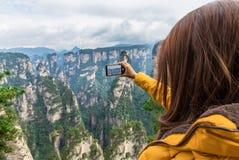 拍照片的亚裔旅游女孩使用智能手机在张集 图库摄影