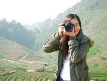 拍照片的亚裔旅游妇女背包徒步旅行者在山自然 库存照片