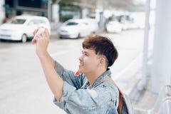 拍照片的亚裔男性旅行家,当等待出租汽车在时 库存照片