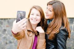 拍照片的他们自己的二个青少年的女孩使用片剂个人计算机 库存照片