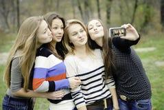 拍照片的他们自己的四个青少年的女孩 免版税库存照片