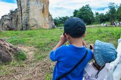 拍照片的后面观点的亚裔孩子由照相机 免版税库存图片