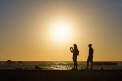 拍照片的夫妇剪影由海 免版税库存图片