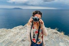 拍照片的女孩户外在一台减速火箭的照相机一次暑假 免版税库存照片