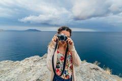 拍照片的女孩游人户外在一台减速火箭的照相机 免版税库存图片