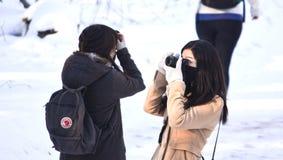 拍照片的女性摄影师在冬天游览时 免版税库存照片