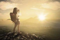 拍照片的女性背包徒步旅行者在山 免版税图库摄影