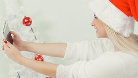 拍照片的她自己的圣诞老人帽子的女孩使用电话 免版税图库摄影