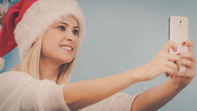 拍照片的她自己的圣诞老人帽子的女孩使用电话 免版税库存照片