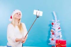 拍照片的她自己的圣诞老人帽子的女孩使用selfie棍子 图库摄影
