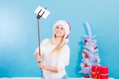 拍照片的她自己的圣诞老人帽子的女孩使用selfie棍子 免版税图库摄影