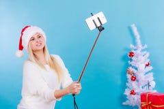 拍照片的她自己的圣诞老人帽子的女孩使用selfie棍子 免版税库存照片