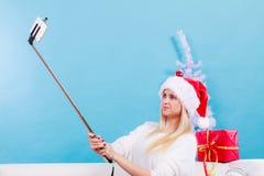 拍照片的她自己的圣诞老人帽子的女孩使用selfie棍子 免版税库存图片