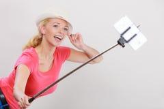 拍照片的她自己的妇女与在棍子的电话 库存图片