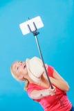 拍照片的她自己的妇女与在棍子的电话 免版税库存照片