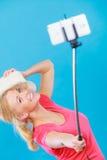 拍照片的她自己的妇女与在棍子的电话 免版税图库摄影
