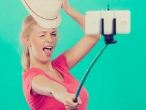 拍照片的她自己的妇女与在棍子的电话 图库摄影