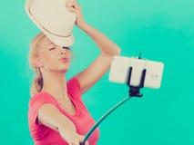 拍照片的她自己的妇女与在棍子的电话 免版税库存图片