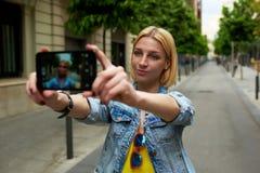 拍照片的她自己的时髦的女性行家在巧妙的电话 免版税库存图片