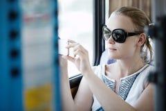 拍照片的妇女在她的在公共汽车的机动性 免版税库存照片