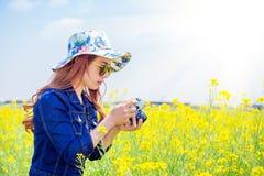 拍照片的妇女在油菜籽开花 免版税库存图片
