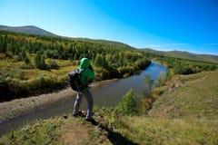 拍照片的妇女摄影师在秋天森林里 免版税库存照片