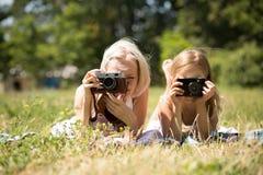 拍照片的妈妈和女儿说谎在毯子在公园 图库摄影