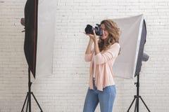 拍照片的少妇使用在stu的一台专业照相机 免版税库存图片