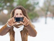 拍照片的少妇使用手机在冬天公园 免版税库存照片