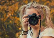 拍照片的少妇摄影师室外 免版税图库摄影