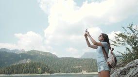 拍照片的少妇由在Mountain湖前面的智能手机 花费在Moutain的美丽的白种人女孩时间 库存图片