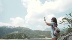 拍照片的少妇由在Mountain湖前面的智能手机 花费在Moutain的美丽的白种人女孩时间 免版税库存图片