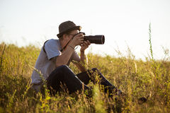 拍照片的帽子的年轻男性摄影师,坐在领域 图库摄影